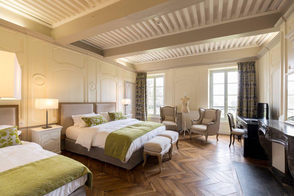 Suite composée de deux un lit. Un lit double et un lit simple. Chambre dans les tons blanche, verte. La boiserie est très importante : moulure sur les murs, poutre apparentes et parquet en point d'hongrie. Suite nuptiale