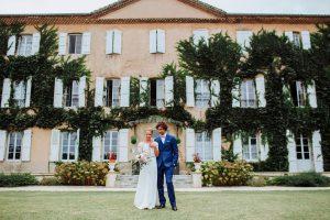 Séance photo des mariés dans le parc du Château de Césarges, avec la façade en fond. Le marié a un costume bleu électrique trois pièces et la mariée une robe bohème et un bouquet de fleurs rose et blanc.