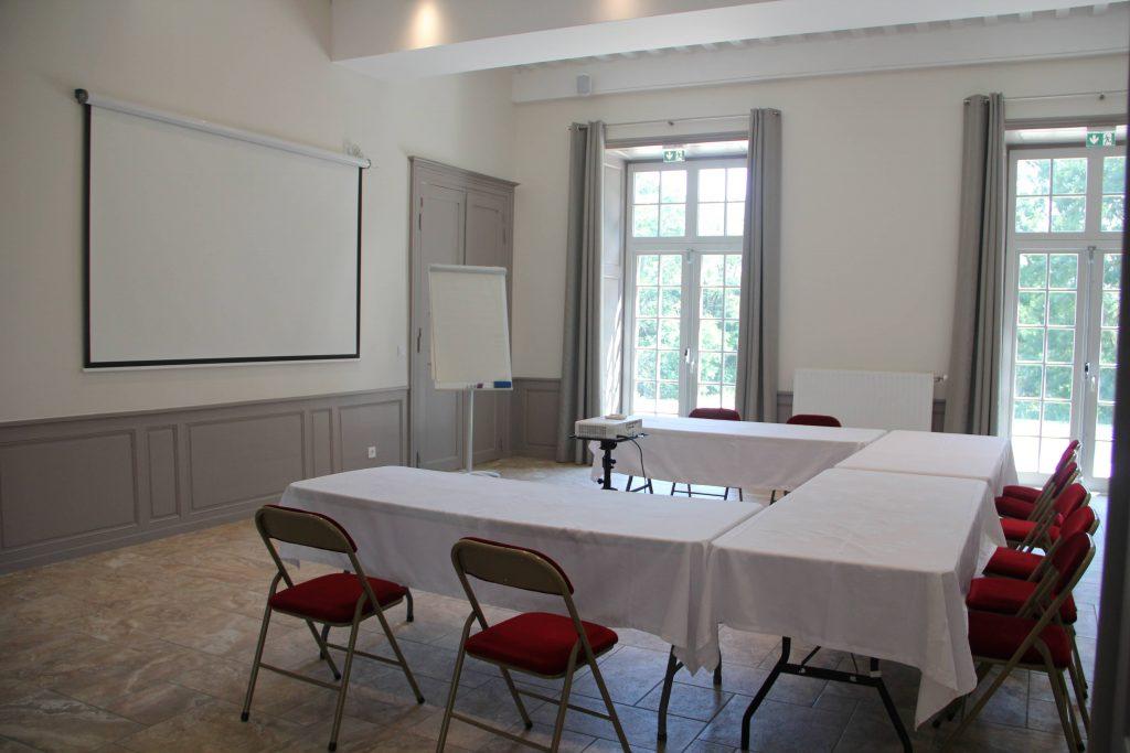 Salle de réunion composé d'un écran de vidéo projecteur, d'un paper board. Les tables sont disposées en U avec des chaises rouges.