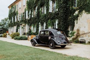 Photo de la voiture des mariés garée devant l'entrée du chateau. Voiture ancienne année 30 noire